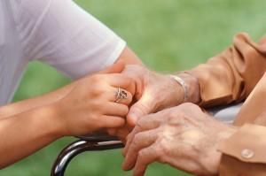 Caregiver-Holding-Seniors-Hand-300x199
